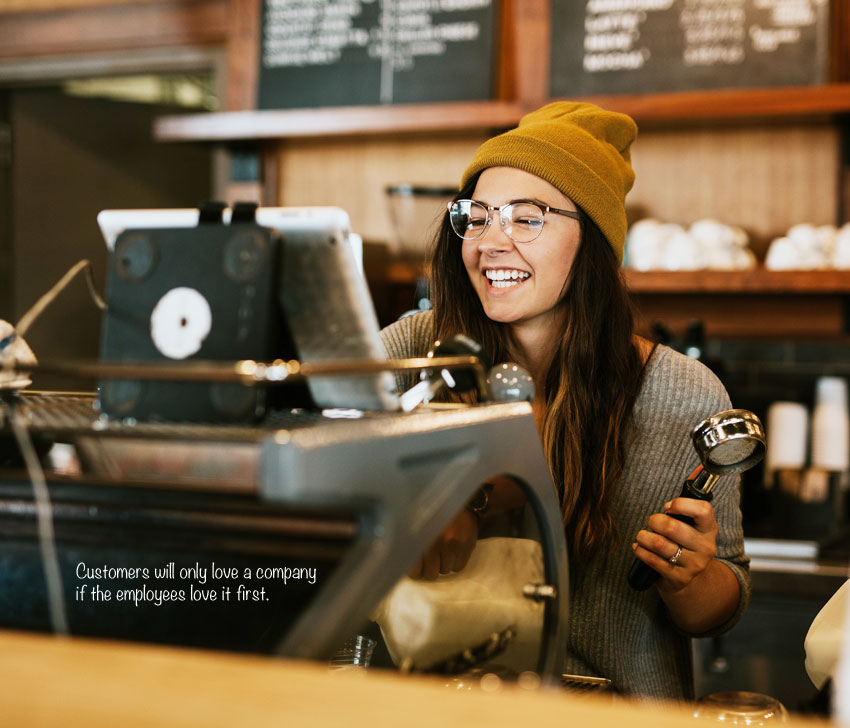 female employee behind the counter, smiling, pleased with our payroll services